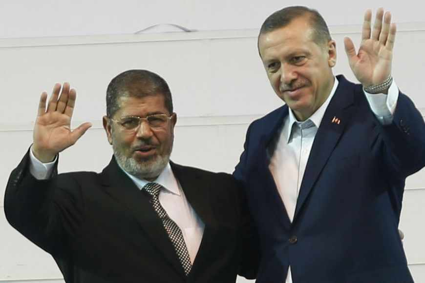 Turkey's Prime Minister and leader of ruling Justice and Development Party (AKP) Tayyip Erdogan (R) and his guest, Egypt's President Mohamed Mursi greet the audience during the AKP congress in Ankara September 30, 2012. REUTERS/Murad Sezer (TURKEY - Tags: POLITICS) - RTR38LZD