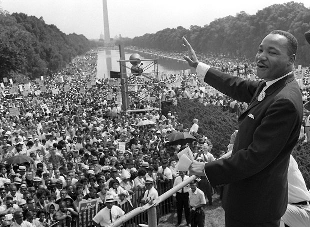 : WASHINGTON, UNITED STATES: US civil rights leader Martin Luther King,Jr. (C) waves to supporters from the steps of the Lincoln Memorial 28 August 1963 on the Mall in Washington DC (Washington Monument in background) during the 'March on Washington'. 28 August marks the 40th anniversary of the famous 'I Have a Dream' speech, which is credited with mobilizing supporters of desegregation and prompted the 1964 Civil Rights Act. Martin Luther King was assassinated on 04 April 1968 in Memphis, Tennessee. James Earl Ray confessed to shooting King and was sentenced to 99 years in prison. AFP PHOTO/FILES (Photo credit should read AFP/AFP/Getty Images)