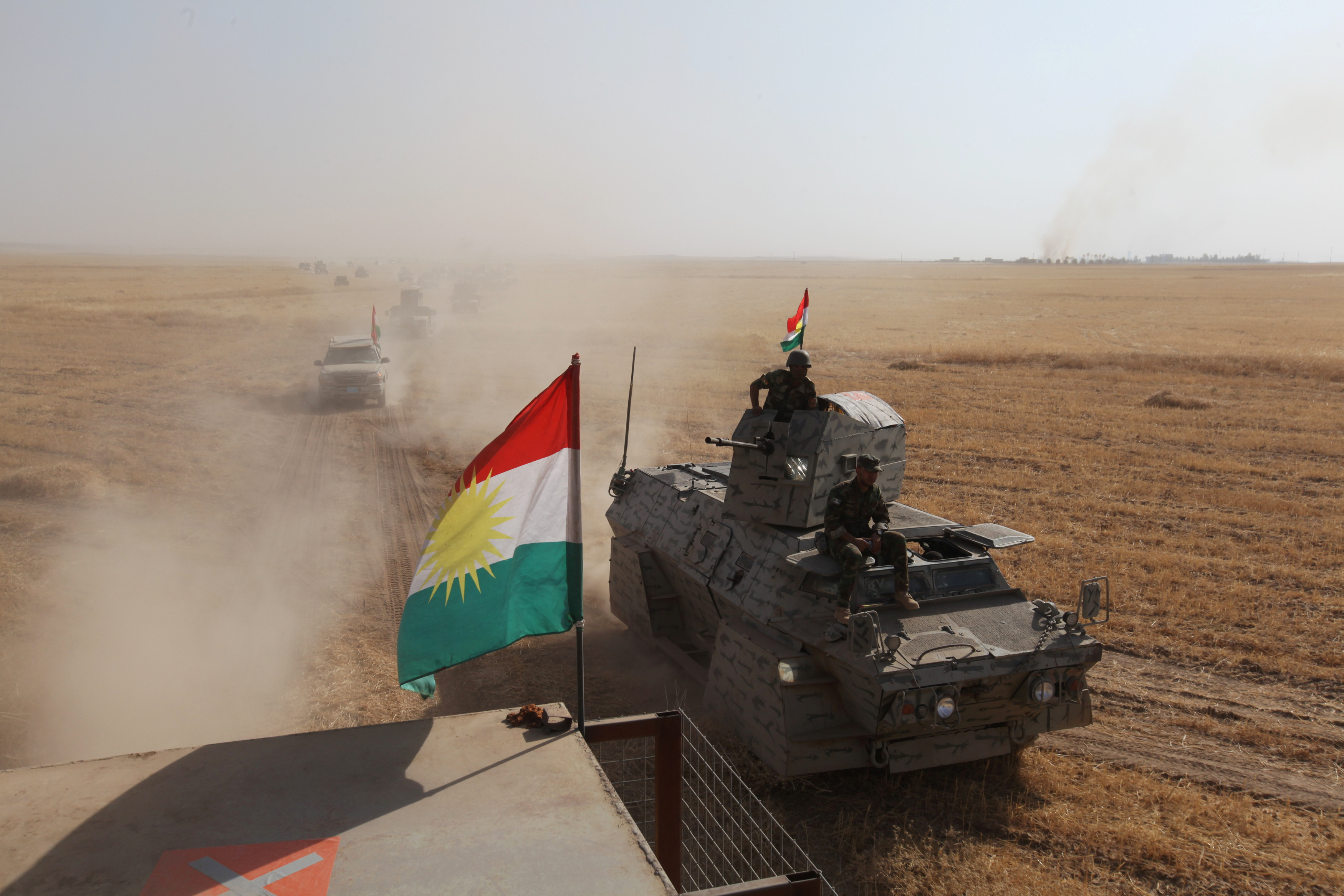 A Kurdish flag is seen on military vehicles of the Kurdish Peshmerga forces on the southeast of Mosul