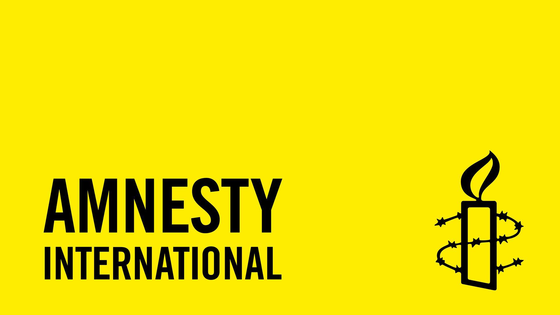 "Yellow background, a candle surrounded by barbed wire mesh, ""Amnesty International"" is written."