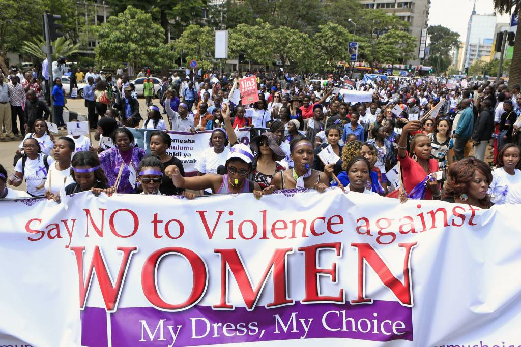 """Φωτογραφία διαδηλωτών με πανό που αναγράφει """"Say no to violence against women. My Dress, My Choice"""""""