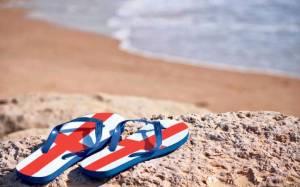 Ένα ζευγάρι σαγιονάρες με σχέδιο την αγγλική σημαία και φόντο μία παραλία